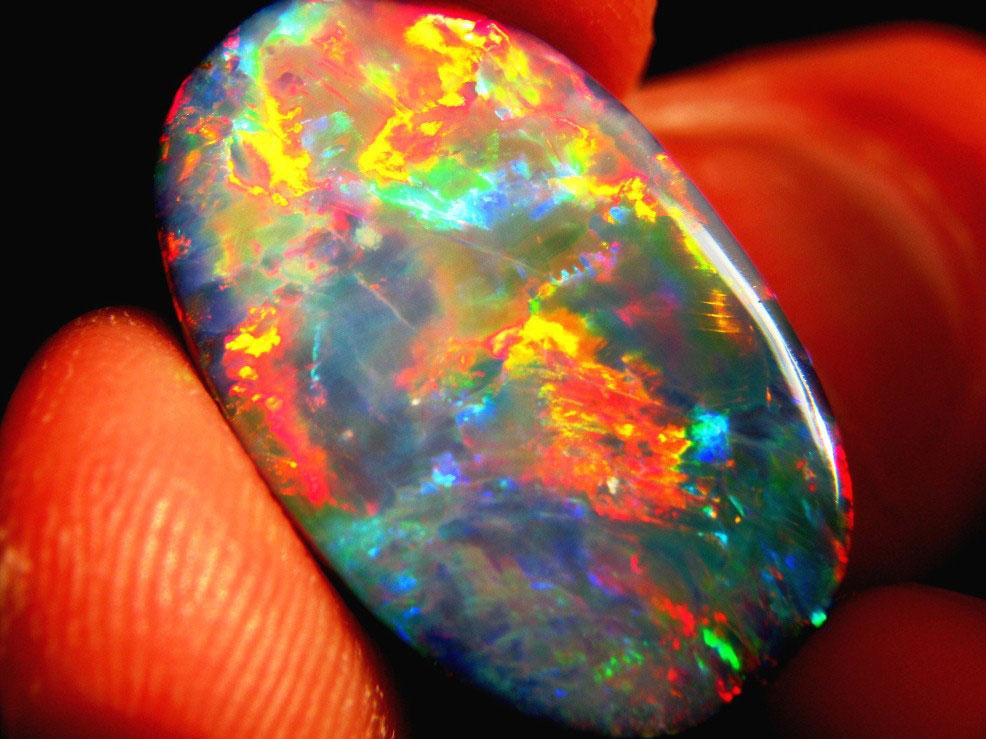 """C'est pour ces pierres aux feux extraordinaires (ici une opale noire de Lightning Ridge) qu'Isabel Gray n'hésita pas à payer de sa personne; elle était obsédée par ces gemmes et se prostitua pour en obtenir des mineurs et prospecteurs passant à sa portée.  Il faut croire que malgré la grande valeur de ces pierres, beaucoup de prospecteurs acceptèrent de s'en séparer pour des moments de plaisir chez la """"reine des opales""""."""