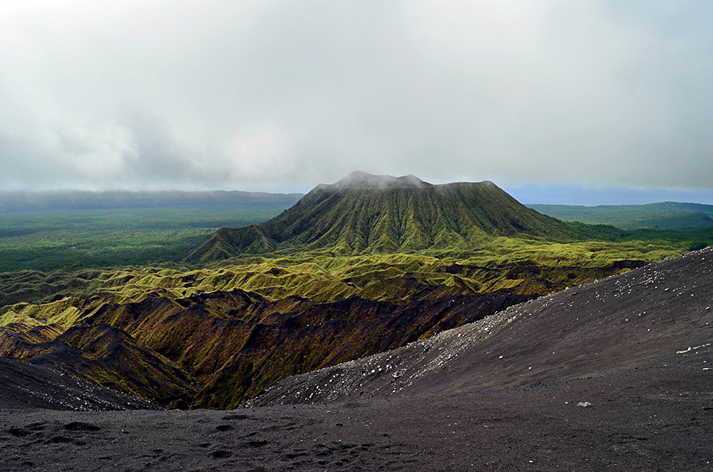 Ambrym est noire comme la peau de sa population mélanésienne, certes, mais elle est surtout noire par l'épaisseur de ses forêts comme par le lourd couvercle de nuages qui en recouvre le sommet bifide.