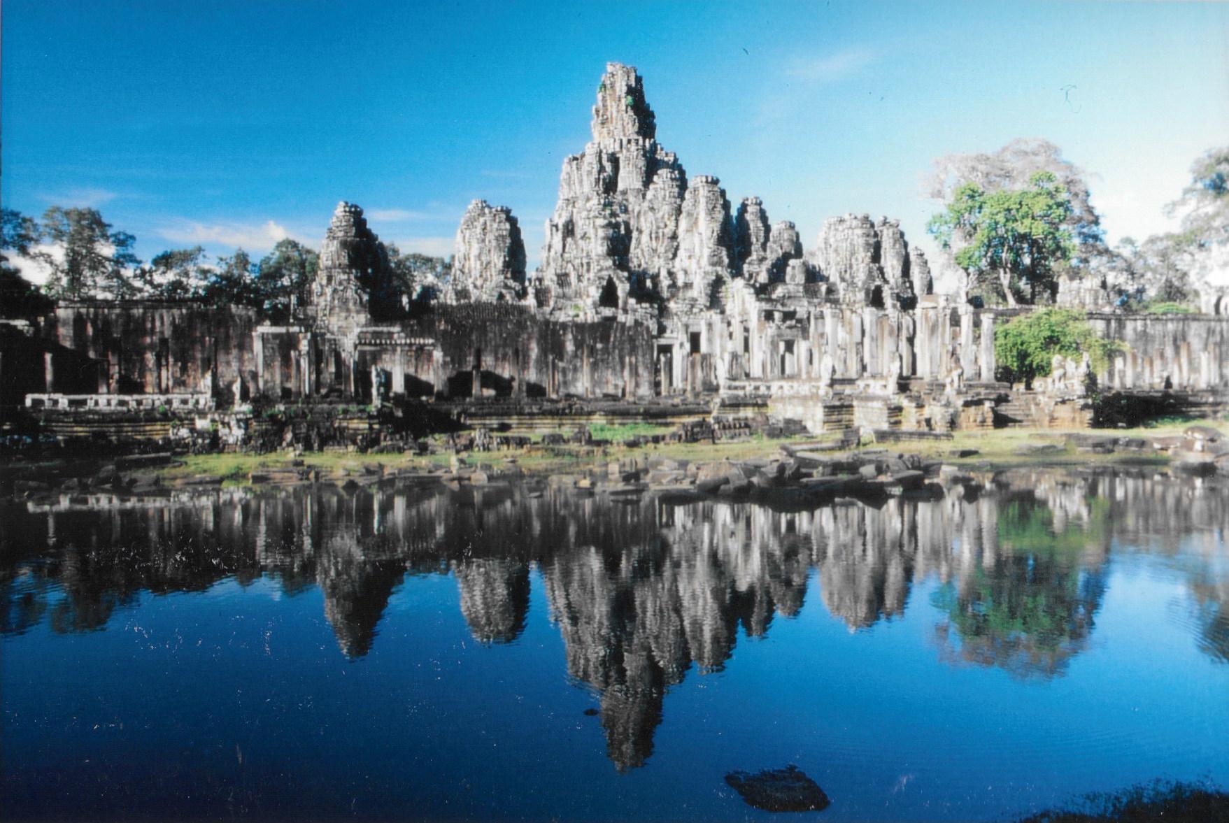 """Le somptueux temple du Bayon se mirant dans les eaux de ses douves. Son nom est dérivé d'une appellation signifiant palais du dieu Indra. Dû à Jayavarman VII, pour un culte bouddhique shivaite, il est daté de la toute fin du XIIe siècle et du début du XIIIe. On écrit Bayon, mais on prononce Bayonne, comme la ville française du Pays basque. Il est situé au centre géographique de l'immense enceinte d'Angkor Thom. Le temple est entouré d'une muraille dont les tours affichent quatre visages apparemment sereins, sinon mystérieusement indifférents. Des """"Mona Lisa"""" asiatiques de pierre en quelque sorte...."""