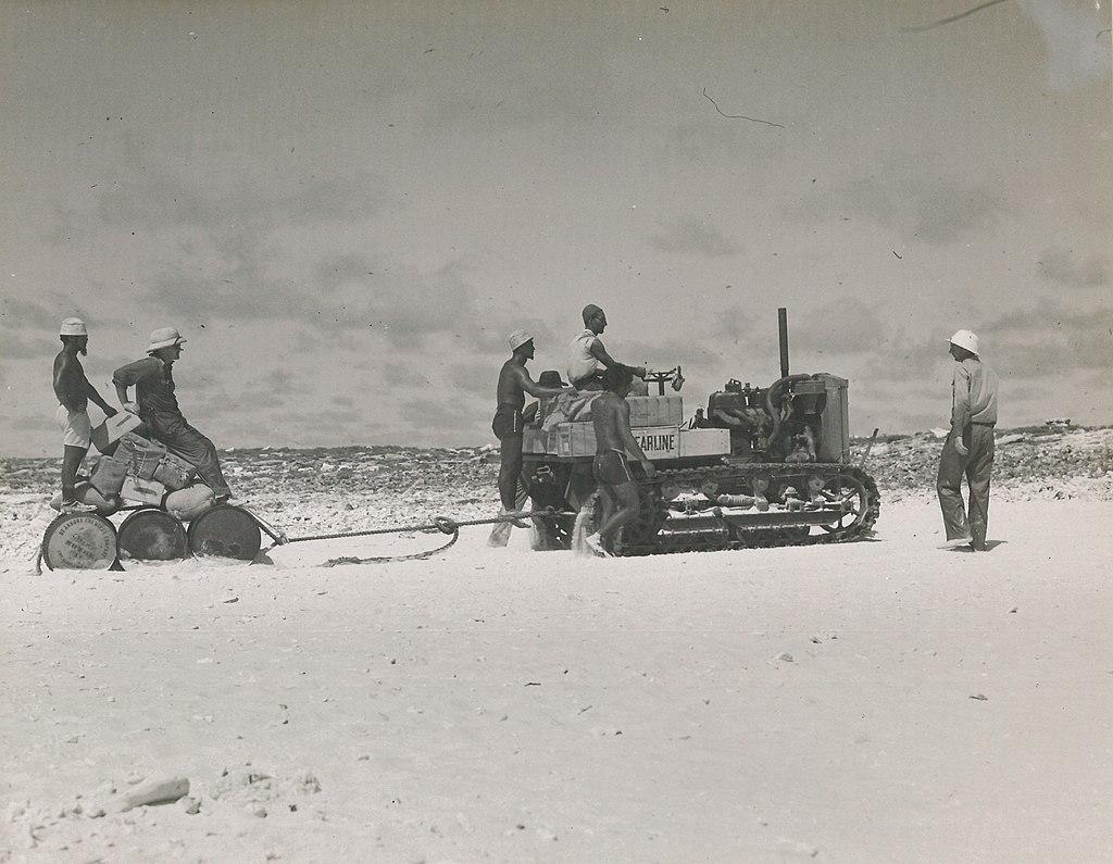 Sur certains de ces atolls colonisés en grand secret, il fallut aménager ce qui devait devenir une piste d'aviation. Un petit engin à chenilles servit à aplanir le terrain et, lorsque le ravitaillement arrivait, à amener au camp les bidons d'eau douce (notre photo, Howland Island).