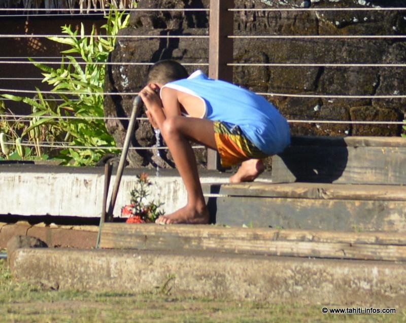 Un enfant boit de l'eau dans les jardins de la mairie de Papeete