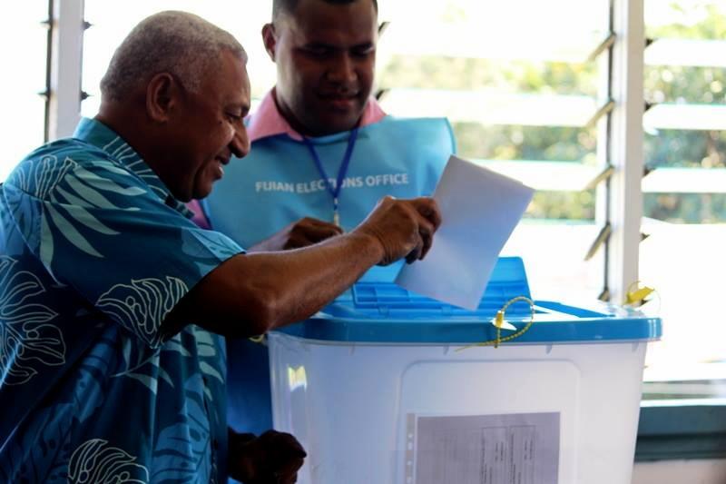 Franck Bainimarama, confiant, glisse son bulletin dans l'urne transparente.