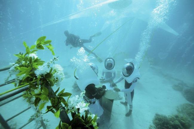 À Bora Bora, les organisateurs de mariage ont l'habitude des demandes extravagantes, cette fois c'est un club de plongée local qui organise des cérémonies nuptiales en scaphandre immergée dans le lagon de Bora. PHOTO GREGOIRE LE BACON, AFP