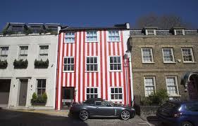 GB: Pour se venger de ses voisins, elle couvre sa maison de rayures rouges