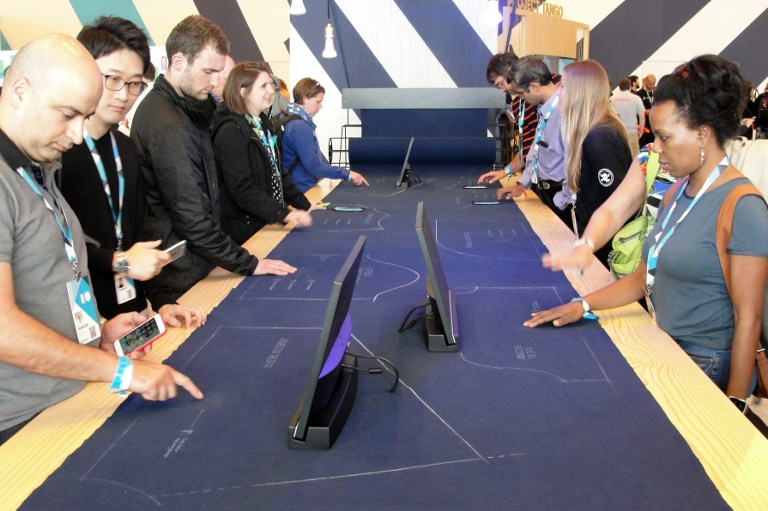 Des testeurs contrôlent un ordinateur en touchant... du tissu ! Crédit GLENN CHAPMAN / AFP