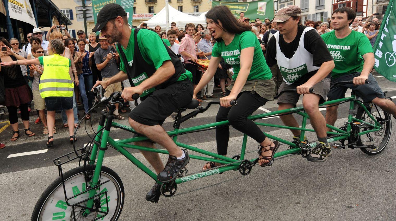 Des gens pédalent sur un vélo à quatre places lors du départ d'un tour de l'Hexagone de 5.600 km pour lutter contre le réchauffement climatique, lancé par le mouvement écologiste Alternatiba, le 5 juin 2015  afp.com/IROZ GAIZKA