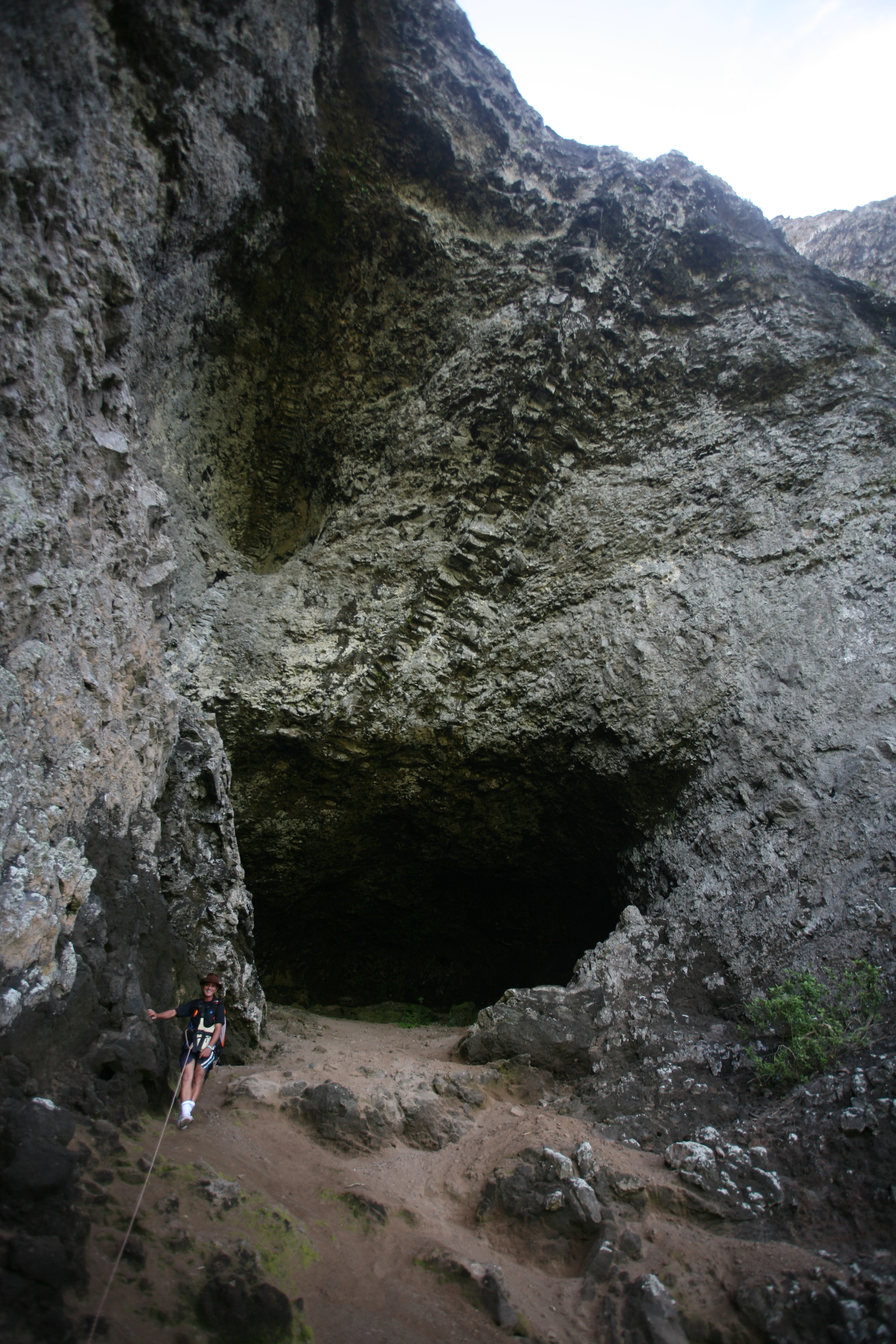 """L'entrée de la grotte lorsque l'on se trouve """"à sa porte"""" ; l'effet d'optique du grand angle la fait paraître petite, mais entre le sol et la voûte, il y a bien vingt mètres de hauteur. Au premier plan, notre guide, Eric."""