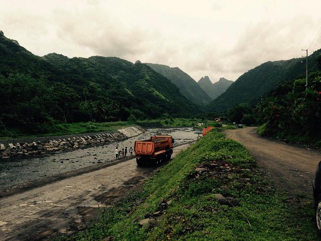 Des camions qui traversent la rivière Taharu'u à gué. Il s'agit de regrouper sur une parcelle privée tous les matériaux extraits lors des travaux. Les travaux d'aménagement de la Taharu'u vont durer jusqu'en 2020 au moins.