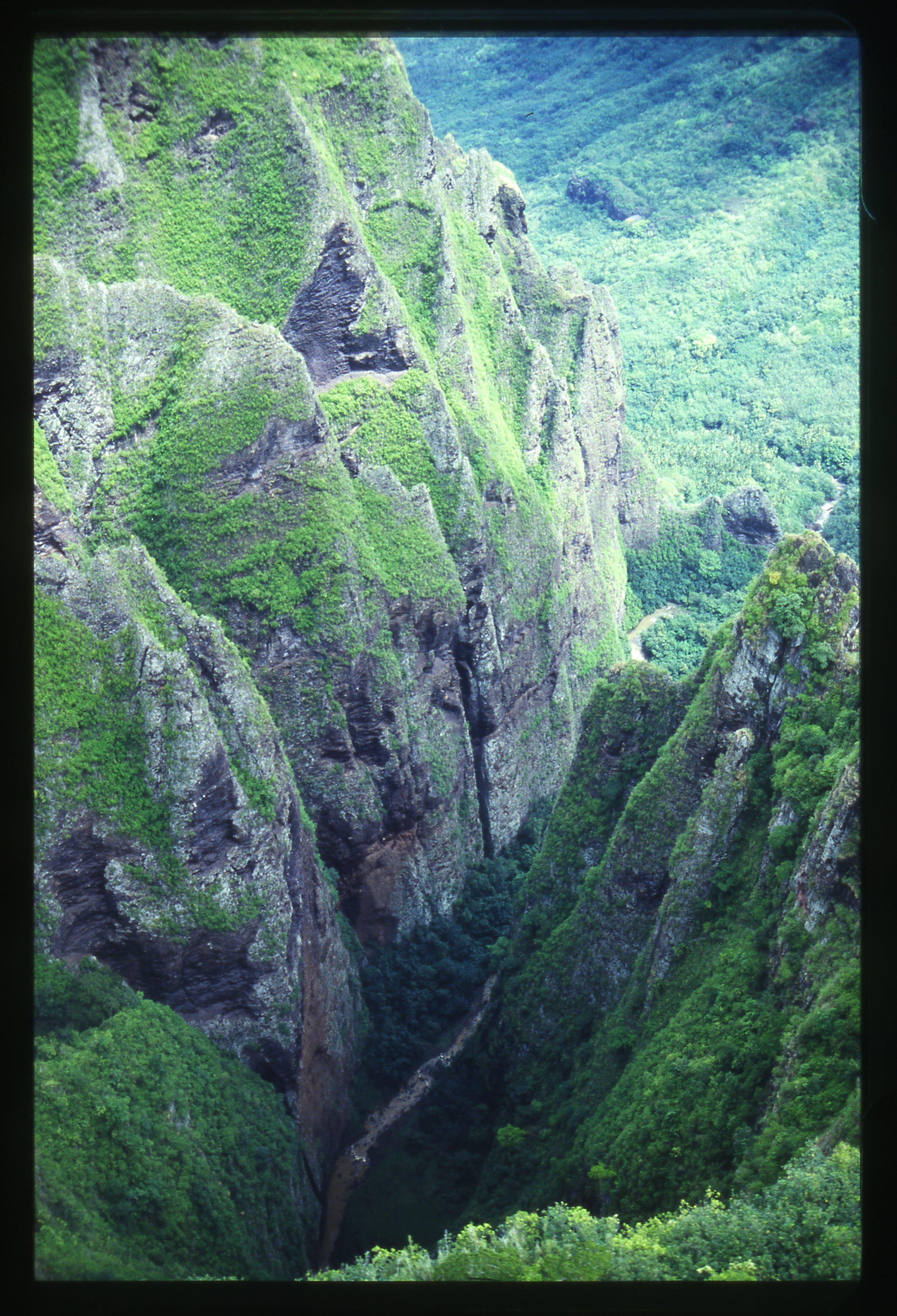 Le haut de la cascade, alors que l'hélicoptère fait un point fixe juste au dessus du vide. 350 m plus bas, on distingue parfaitement le cours d'eau que suivent les randonneurs.