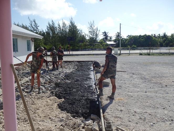 Le détachement coule le béton pour réaliser la dalle de l'ancienne école