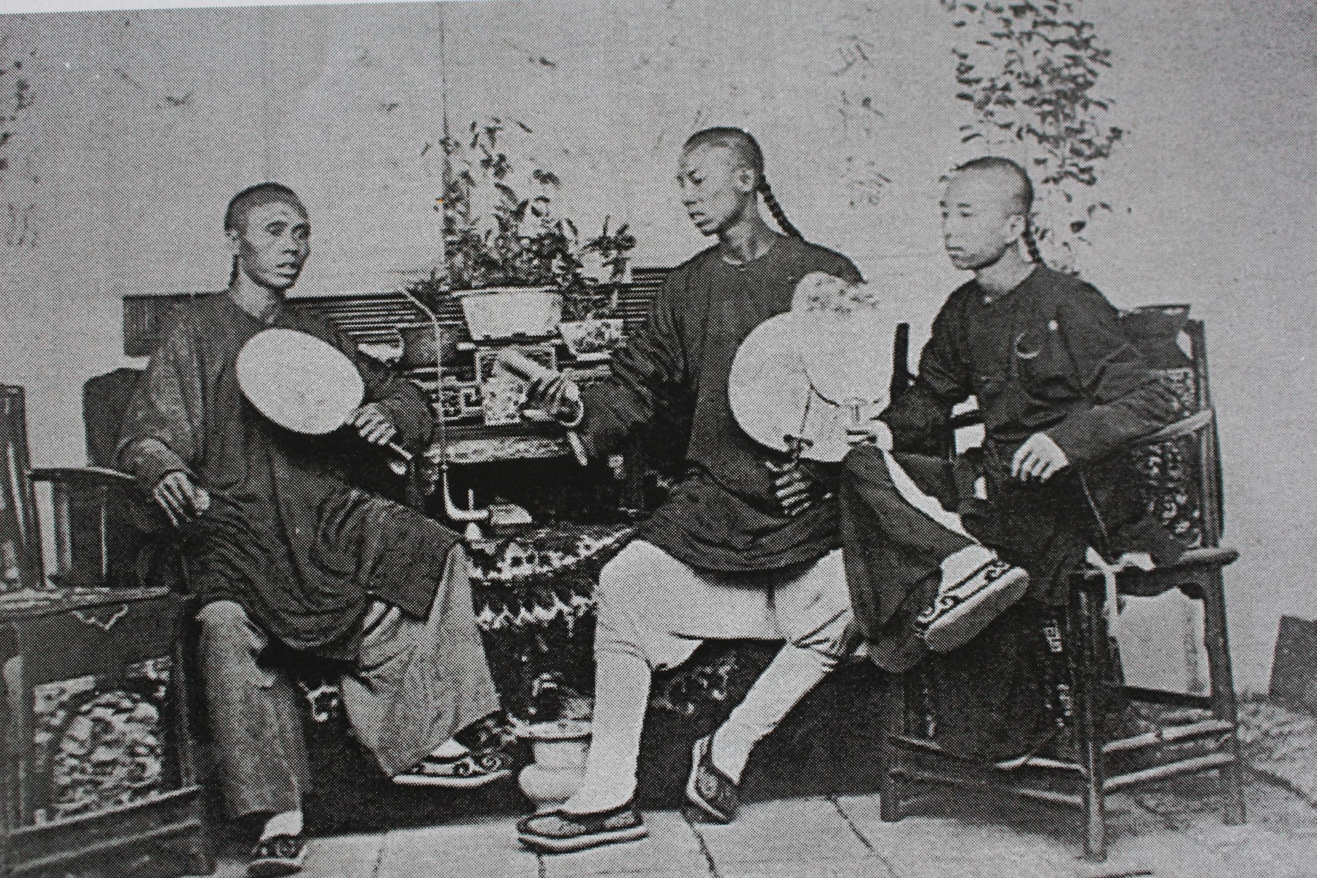 Trois jeunes chinois assis chez eux dans les années 1970. Crédit John Hall.