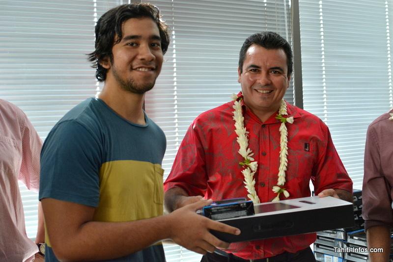 Teva Rohfritsch, ministre de l'Économie numérique, offre à Kiehiva, padawan de la légion des Guardians, l'une des tablettes graphiques et l'un des disques durs de 1 To qu'il a apporté dans sa hotte pour les 22 élèves de Poly3D.