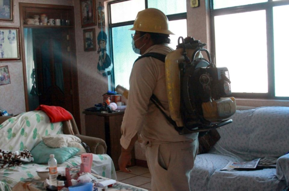 Un agent sanitaire fumige une maison pour lutter contre le moustique Aedes Aegypti, vecteur du virus Zika, le 5 février 2016 à San Lucia del Camino, au Mexique