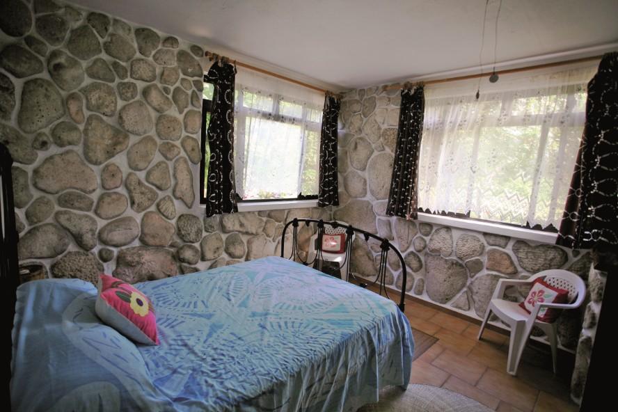 """Une chambre """"cosy"""" à l'ancienne, tout en corail, avec un lit datant du début du XXe siècle, à la pension Teautamatea"""