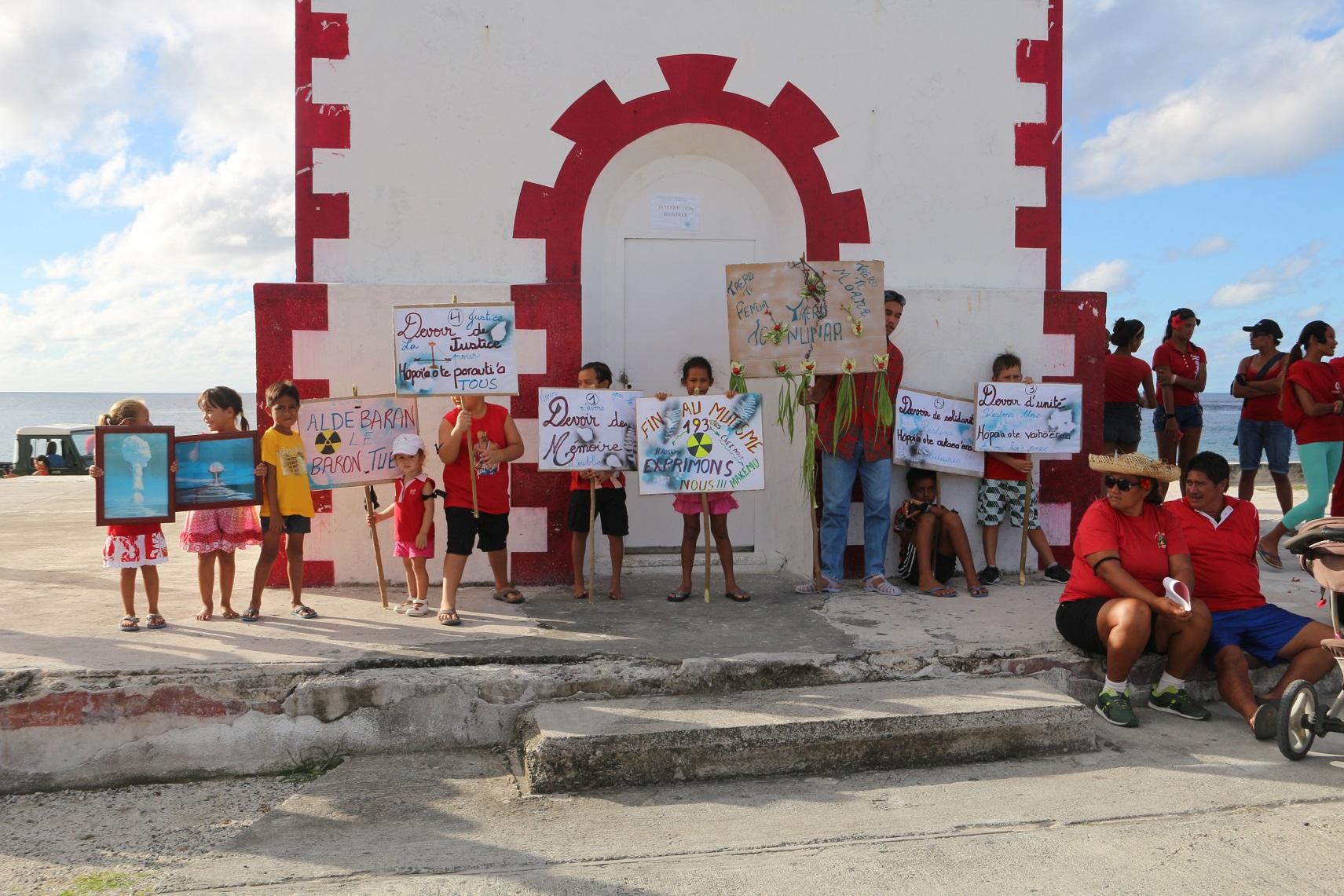 Les enfants de l'atoll se préparent à défiler avec les pancartes. Le point de rendez-vous était donné au phare de l'atoll