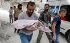 Un homme syrien porte le corps d'un enfant retrouvé sous les décombres d'un bâtiment après un raid aérien le 23 septembre sur la ville d'Alep.