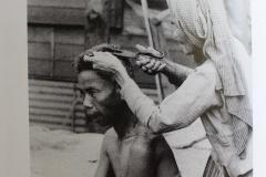 Une femme coupe les cheveux de sa voisine avec des ciseaux de tailleurs.
