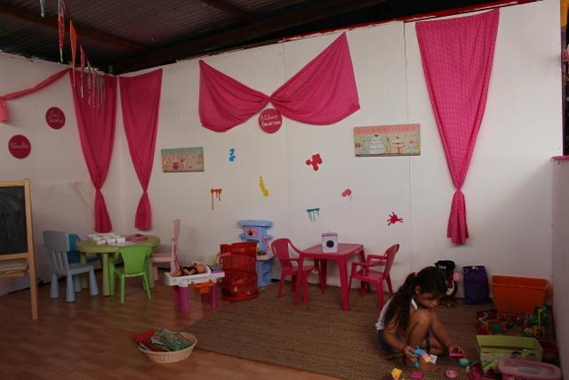 Les p'tits ateliers montent un stand aux couleurs qui font son identité (imprimé rose ou violet à pois blancs, nœuds, mobilier coloré, coin jeux, matériel de bricolage, etc.).